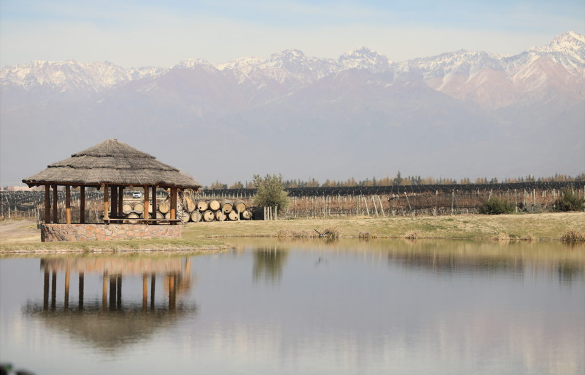 A straw hut in a pond with a scenic view of a large mountain range.
