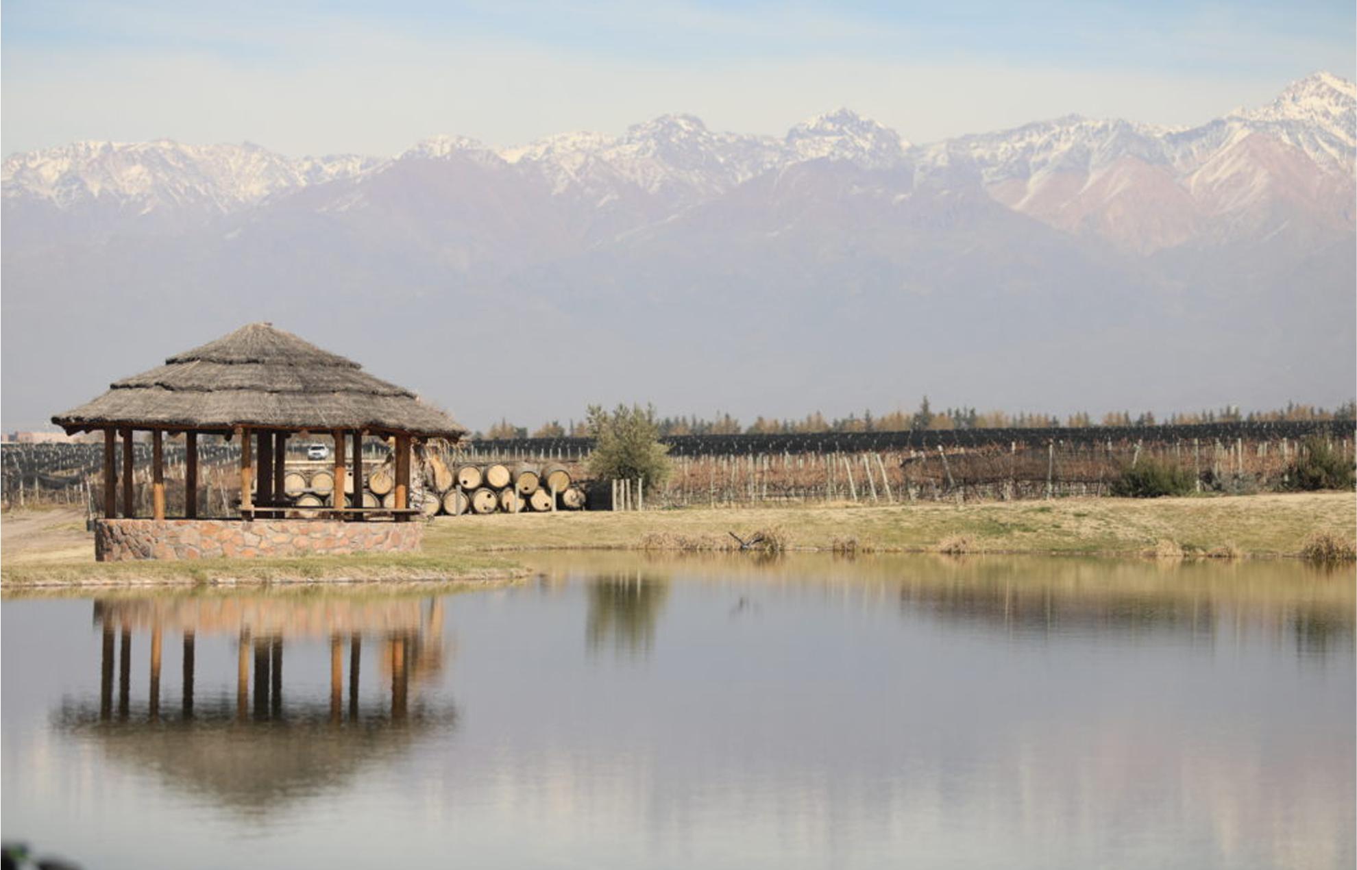 Une paillote située dans un étang avec une vue panoramique sur une grande chaîne de montagnes.