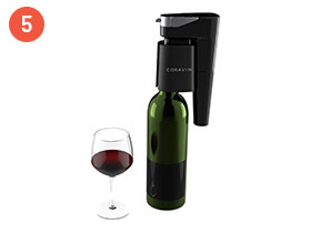 Coravin Model Eleven System on a wine bottle next to a glass of red wine