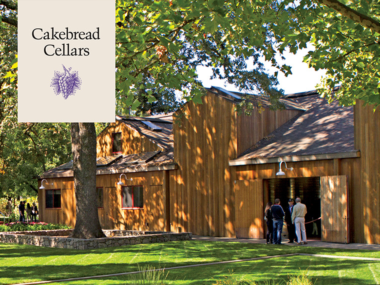 Image of a barn with green grass and people standing outside of it featuring the Cakebread Cellars logo.