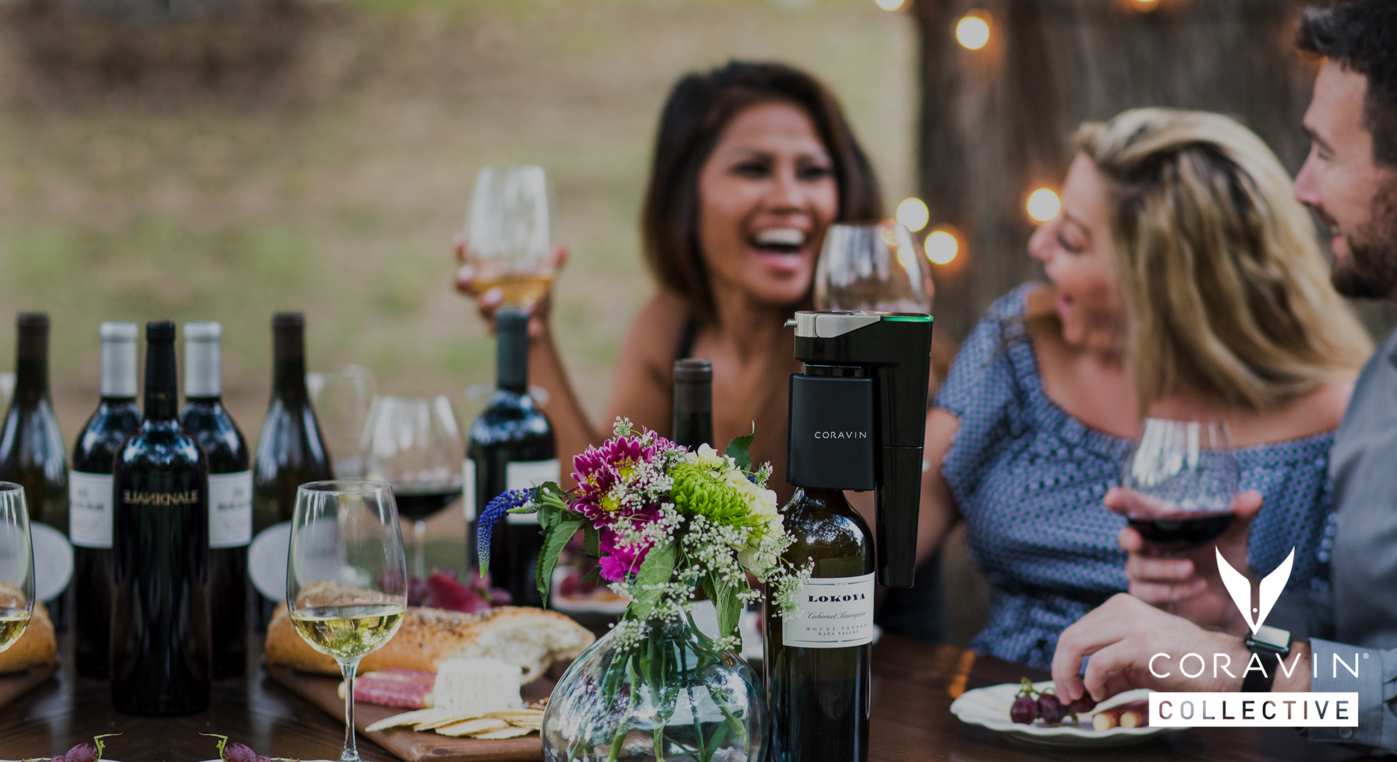 Friends using a Coravin to drink red and white wine outdoors at a picnic table, featuring the Coravin Collective logo.