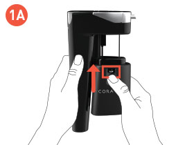 Hands holding the Coravin Model Eleven System, with thumb pushing up on the Clamp Release