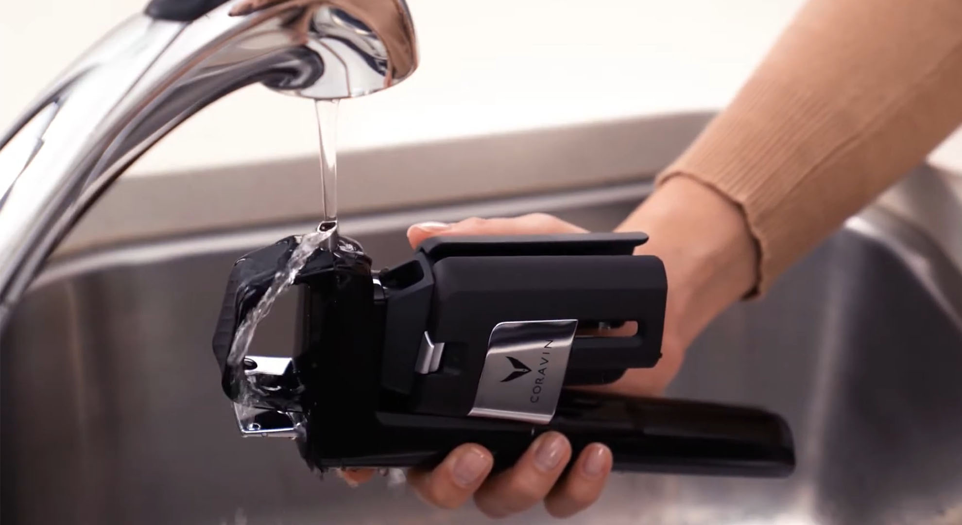 Coravin Model Six Wine Preservation System under a running tap