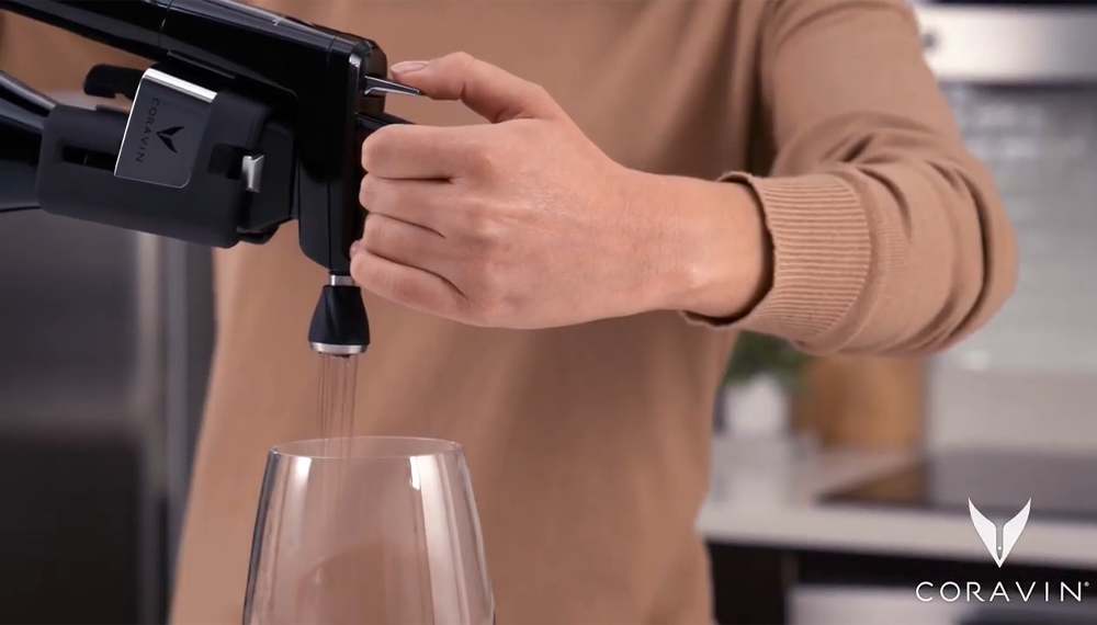 A close up of a woman pouring red wine into a glass using a Coravin Wine Preservation System and Coravin Aerator.