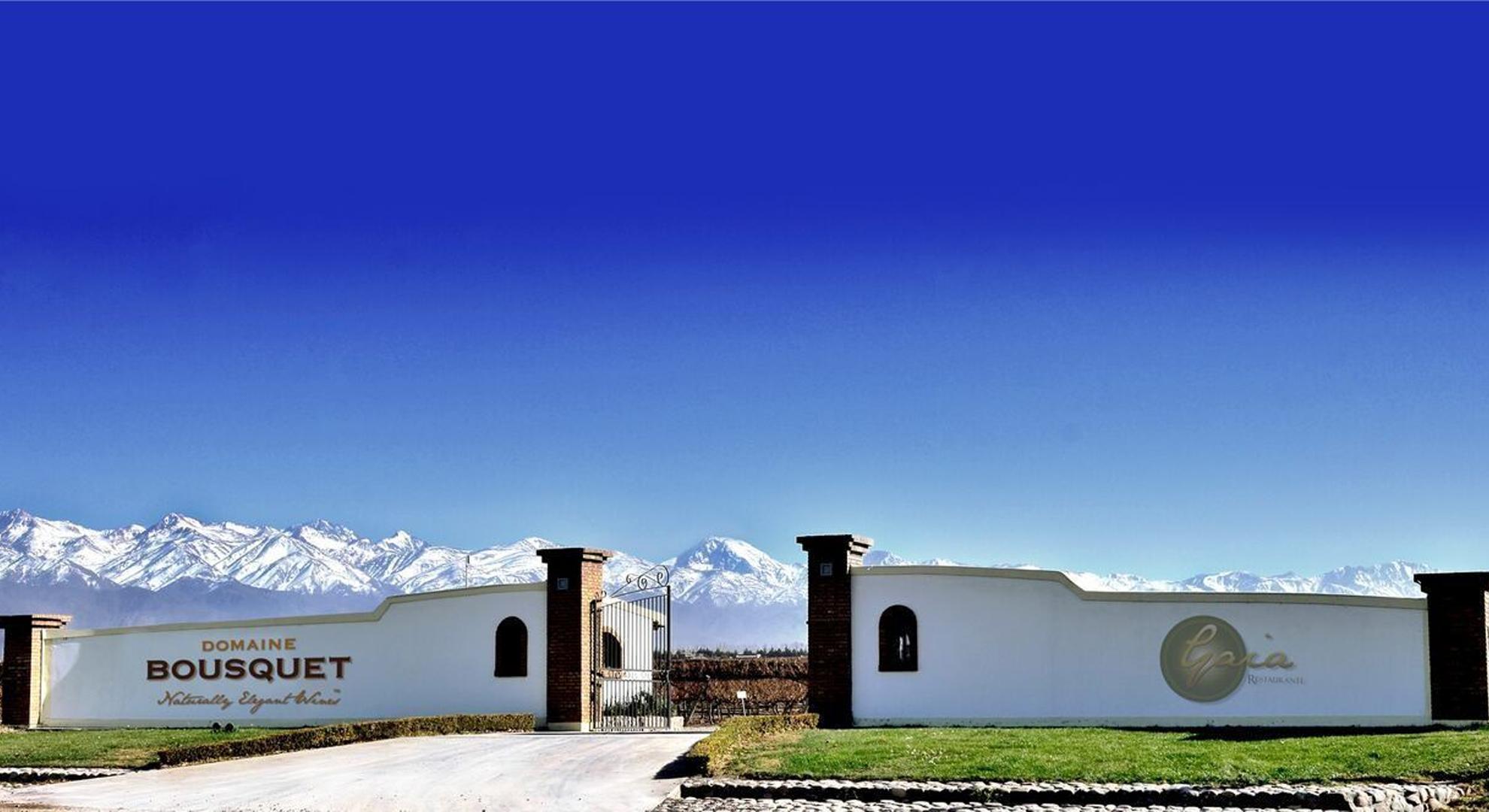 Photo du portail du Domaine Bousquet, avec des montagnes et un ciel bleu.
