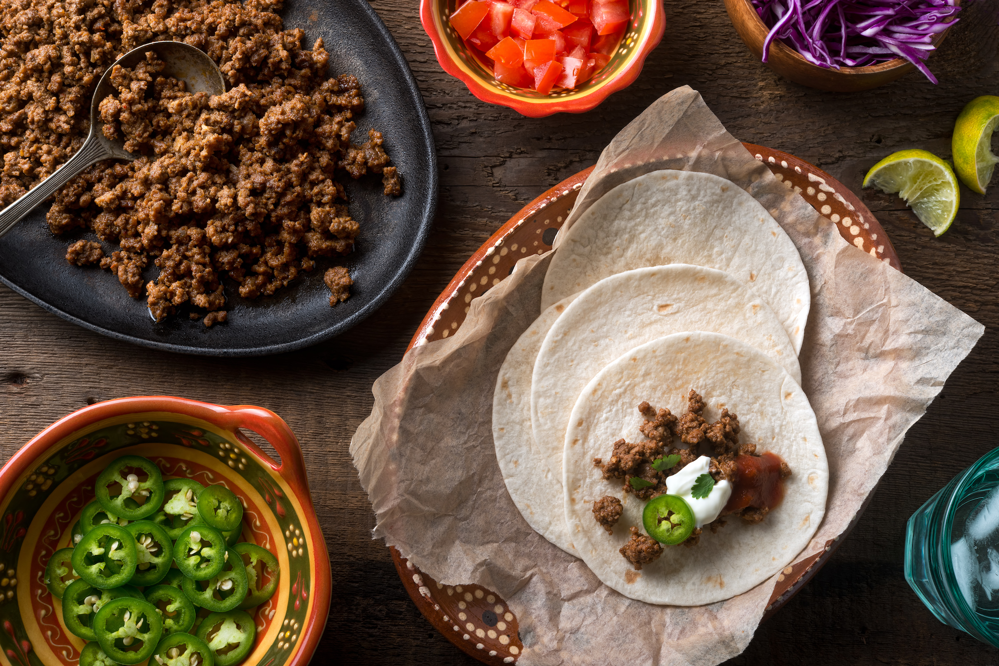 ground beef tacos with tomato lettuce and jalapeno