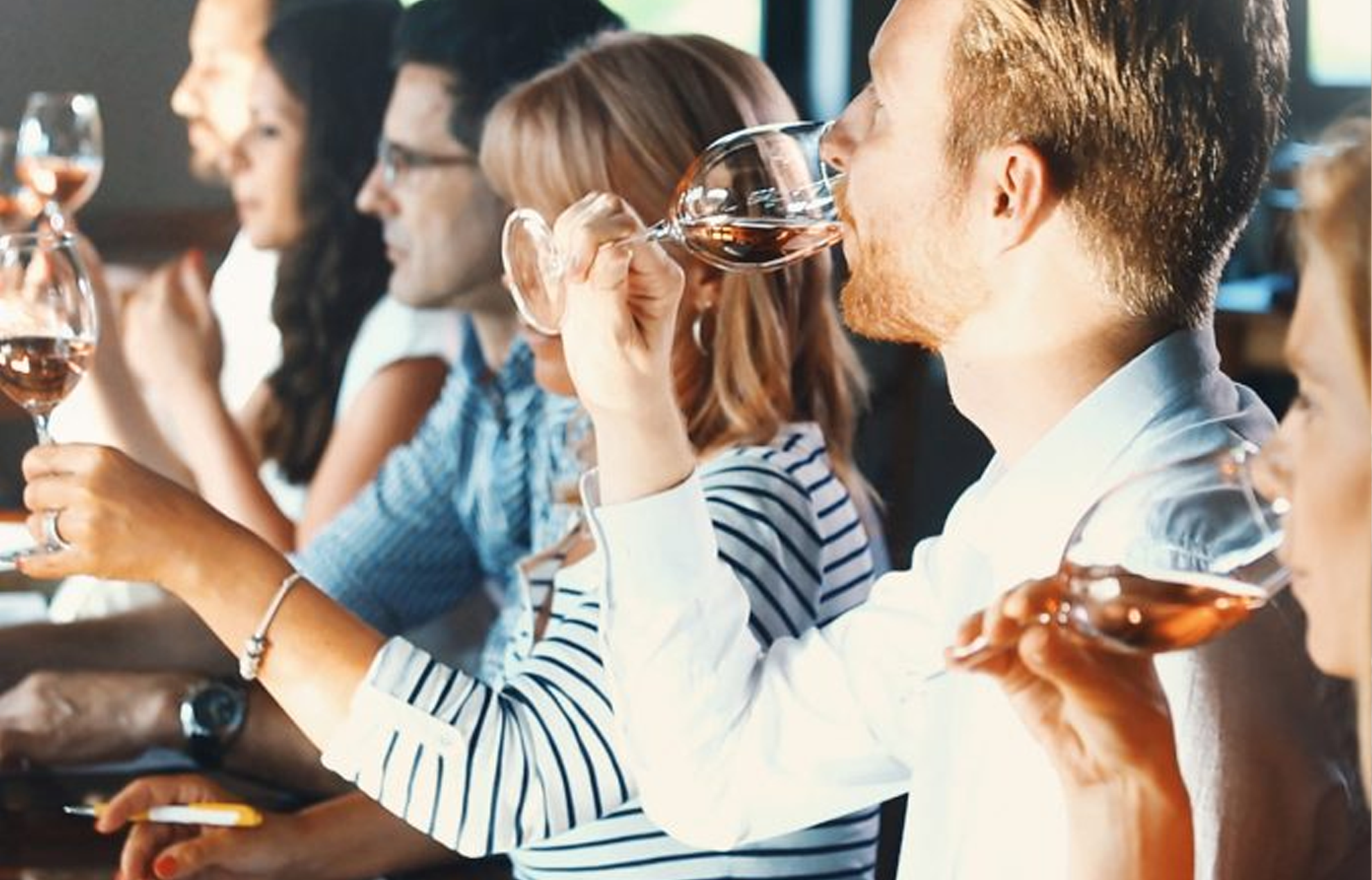Multiple people participating in a wine tasting with each of them tasting a glass of wine.