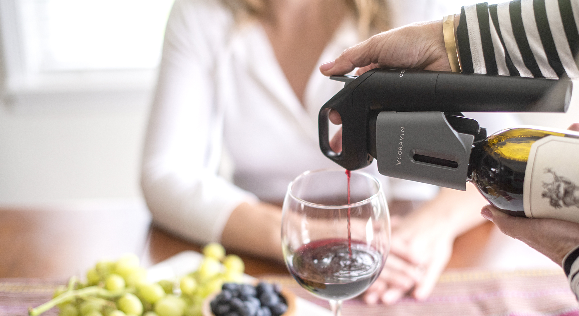 Woman sitting at a table spread of fruit with red wine being poured by a Coravin Wine Preservation System.