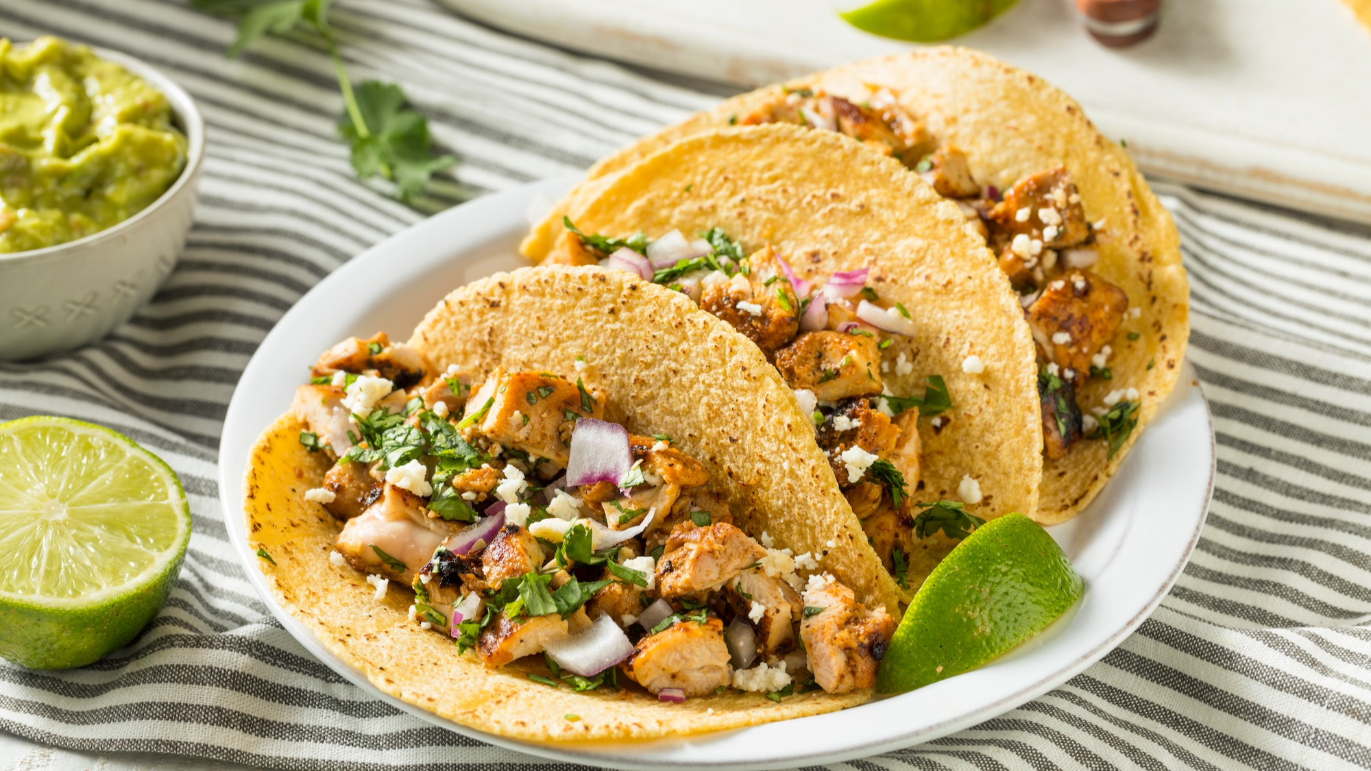chicken tacos with onion and a side of guacamole and lime