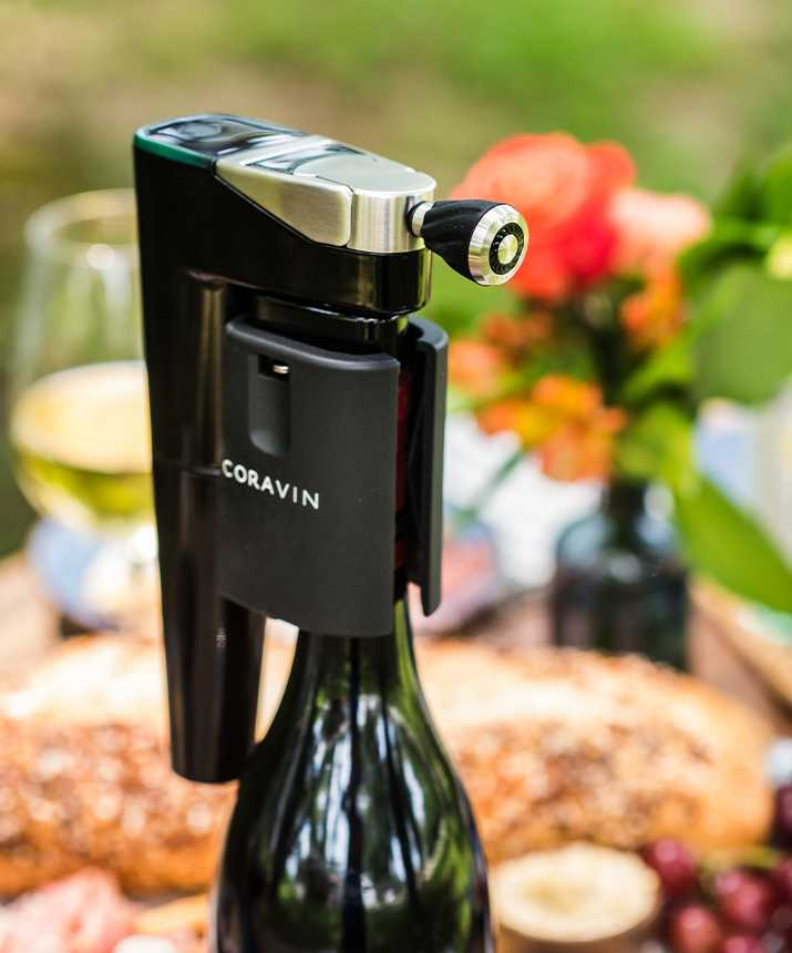 The Coravin Model Eleven on a wine bottle with the Coravin Aerator inserted outside on a table filled with wines and snacks.