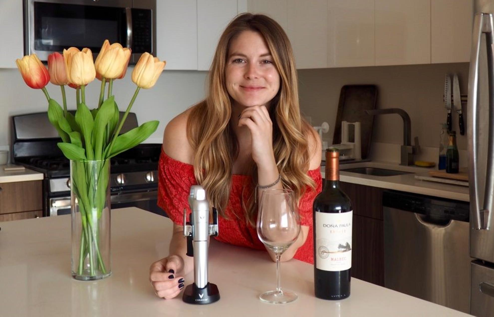 Chelsie Petras de Chel Loves Wine con una copa de vino, una botella de vino y el sistema Coravin sobre la mesa.