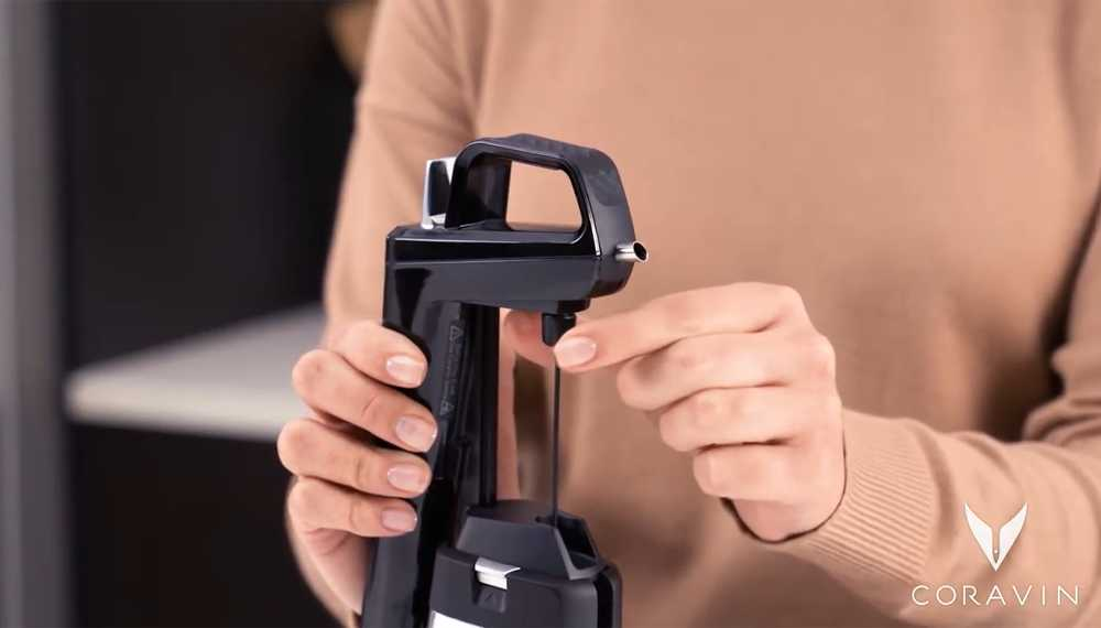 Woman screwing a Coravin needle into a Coravin Wine Preservation System.