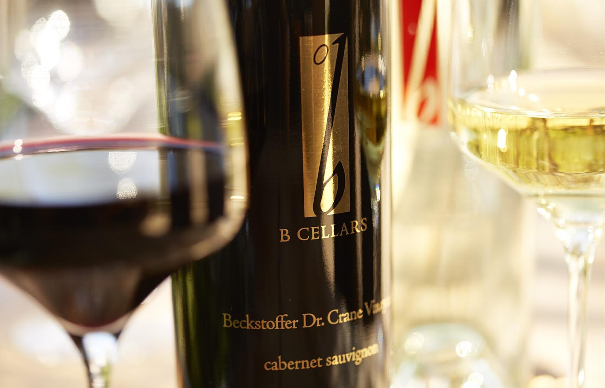 Gros plan sur des verres contenant du vin rouge et du vin blanc, avec une bouteille de vin BCellar.