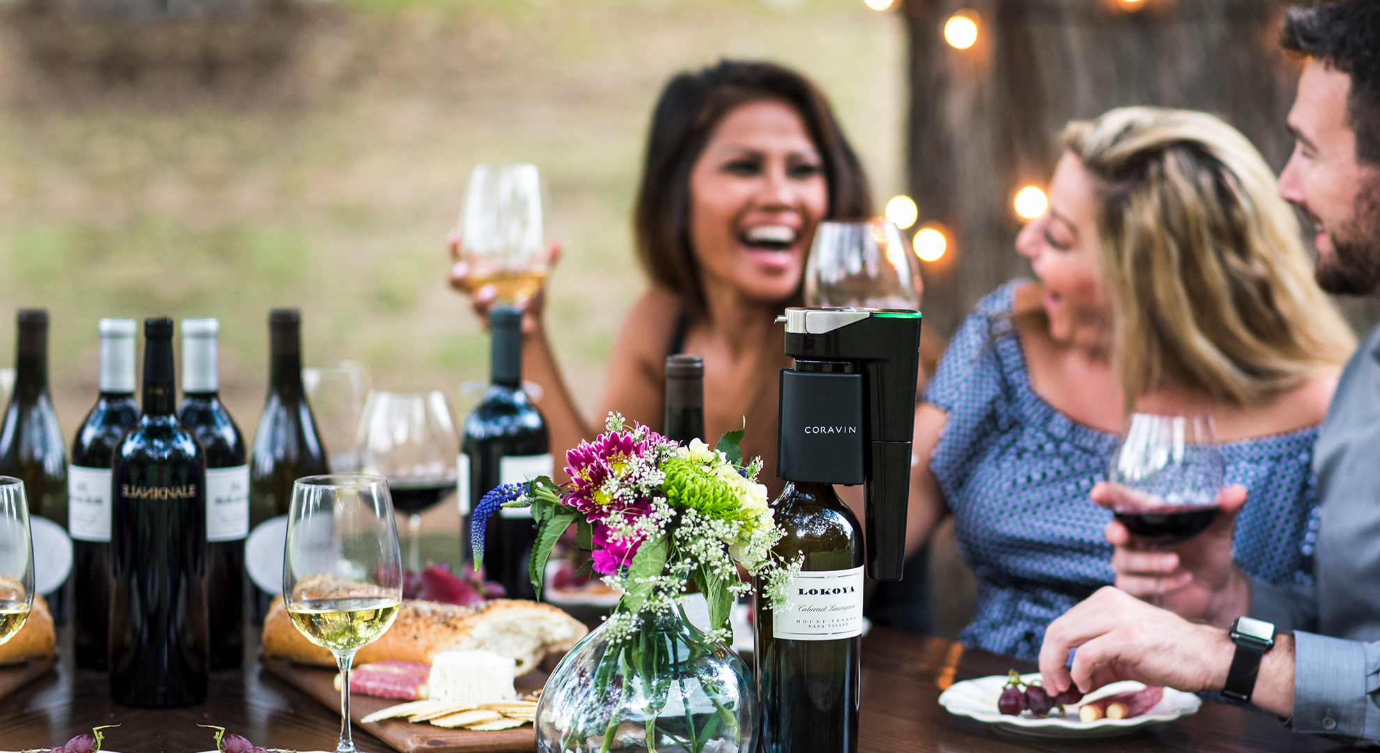 Friends using a Coravin to drink red and white wine outdoors at a picnic table.