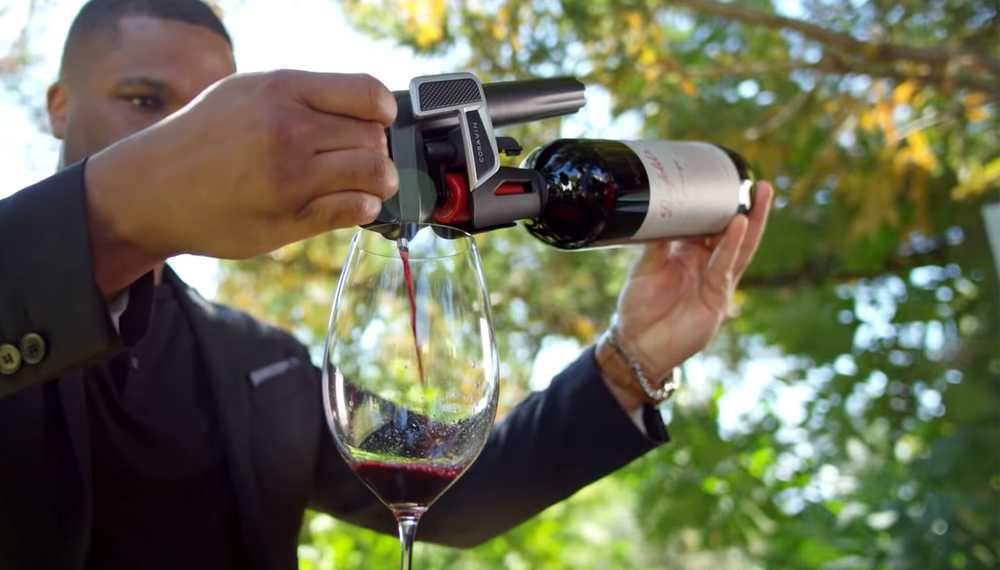 A man pouring red wine into a glass using a Coravin Wine Preservation System.