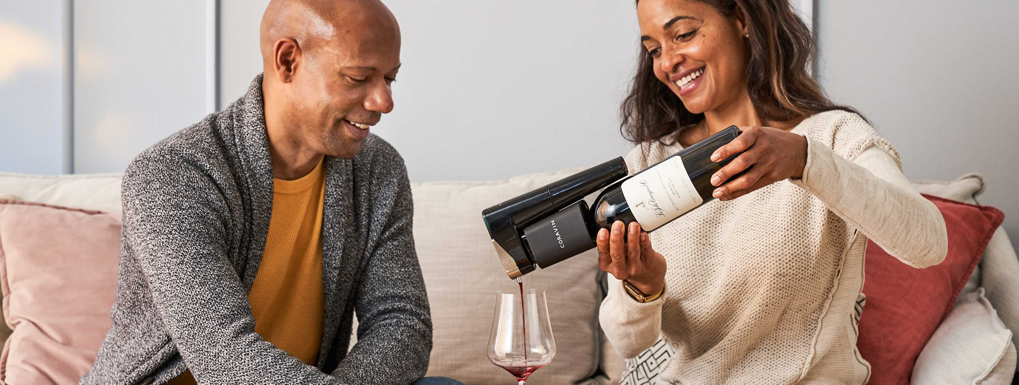 Couple pouring red wine into a glass while sitting on a couch.