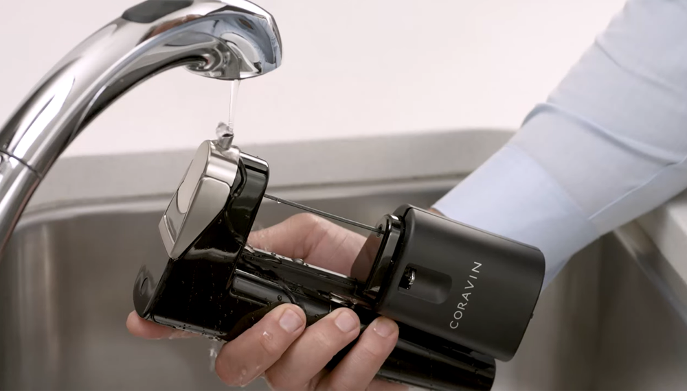 A person holding the Coravin Model Eleven under a sink faucet.