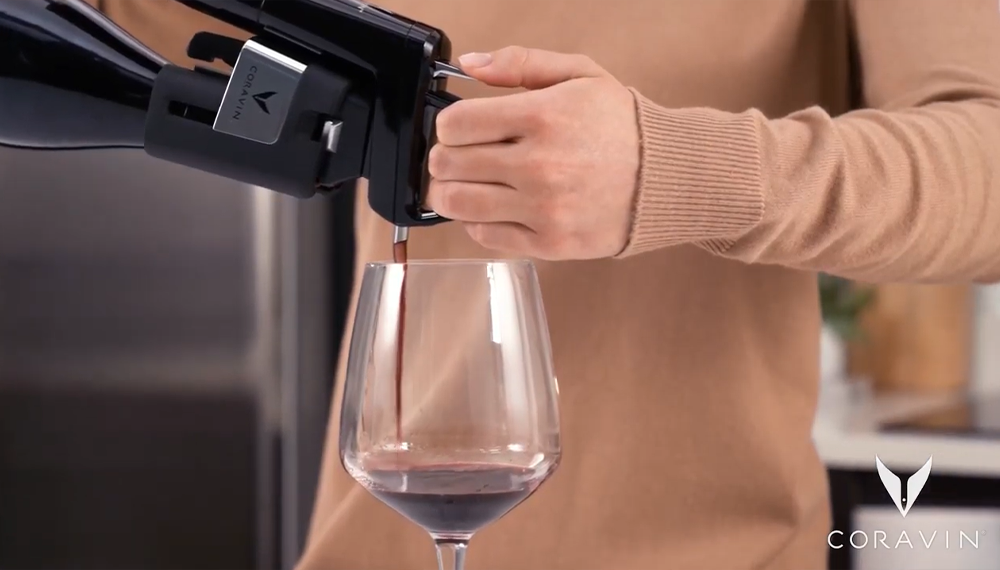 A close-up of a woman pouring red wine into a glass using a Coravin Wine Preservation System.