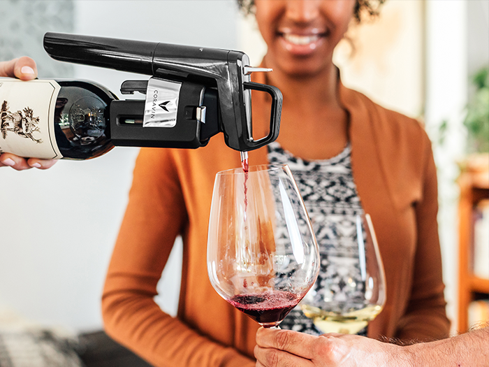Red wine being poured into a glass using a Coravin System, while a woman stands holding a glass of white wine.