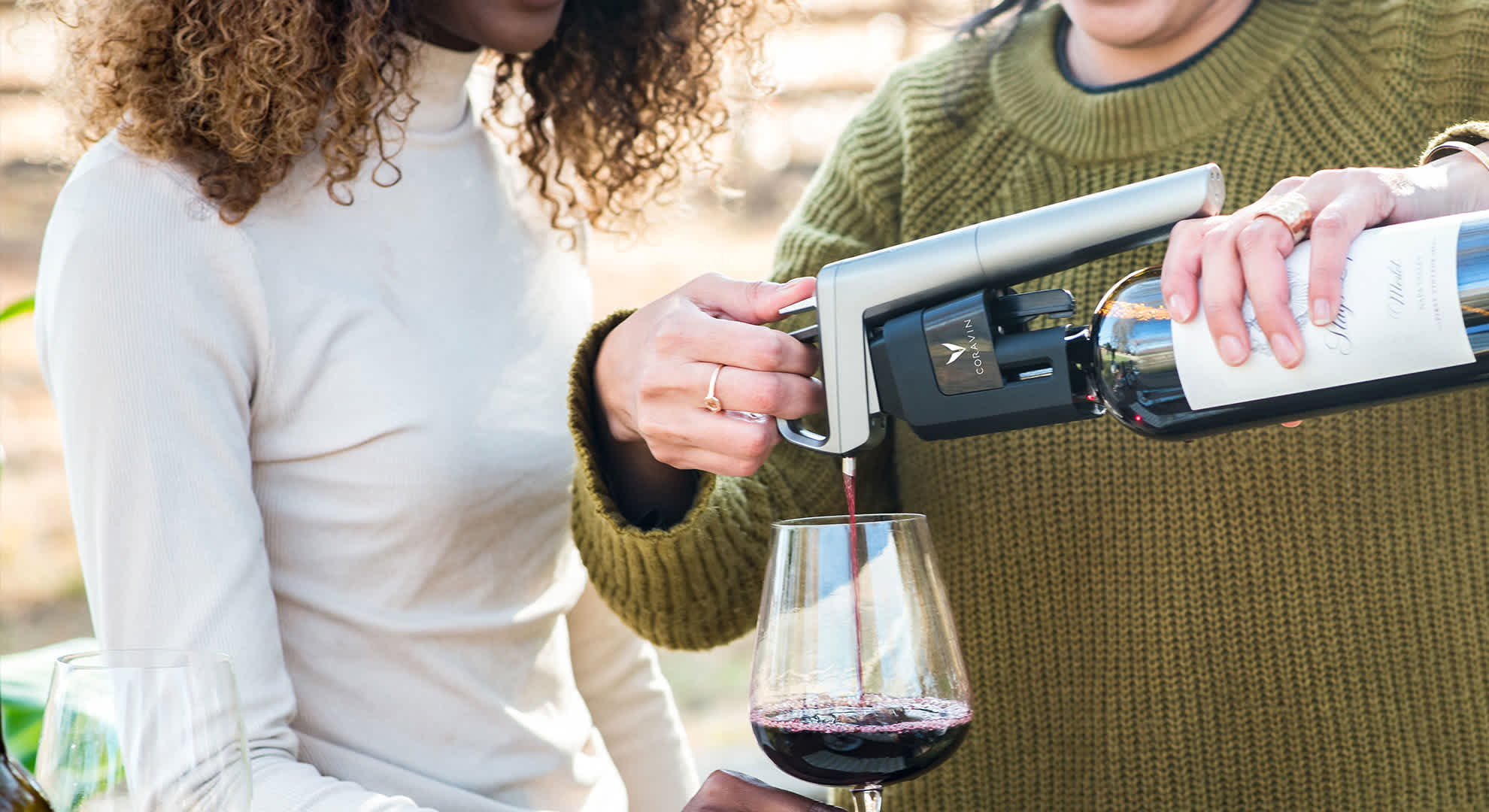Women pouring red wine with the Model Five Wine Preservation System outside
