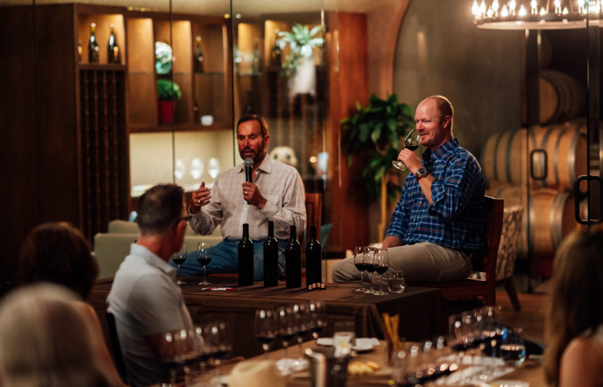 Two men talking in front of a crowd at a wine tasting in a wine cellar.
