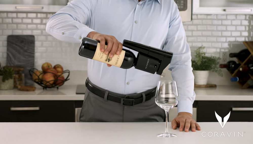 A man pouring wine into a glass using a Coravin Model Eleven Wine Preservation System for automatic pour.
