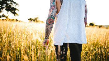 Tattooed man walking in a field
