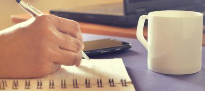 Picture of a hand writing on notepaper