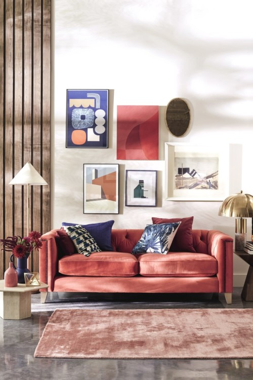 Living space designed by London Interior Designer, Andrew Jonathan Design, for DFS. Styled for the 2019 Look Book, a coral red velvet sofa sits with wood cladding and cone shaped lighting and a living room gallery wall.