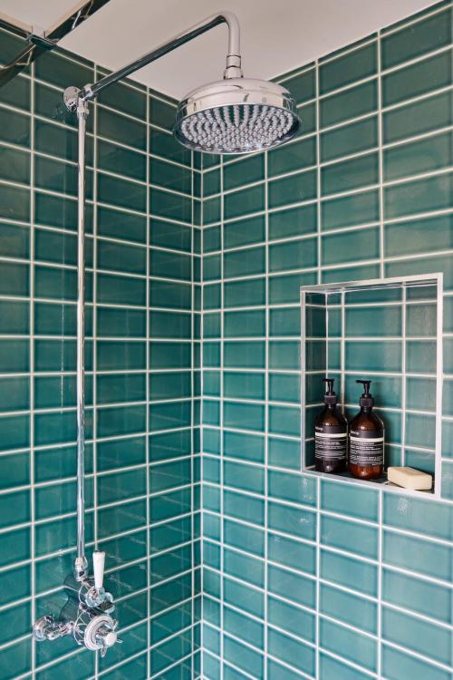 Tiled shower in loft conversion ensuite - teal green tiles and chrome fittings. North London Interior Design