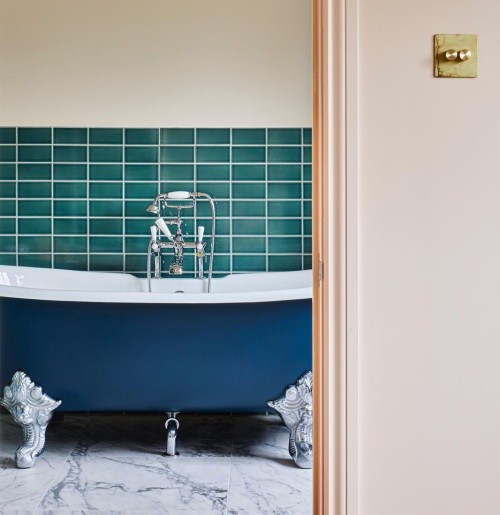 Roll top cast iron bath painted blue, framed by Setting Plaster walls by Farrow & Ball. A London loft conversion ensuite, interior design by Andrew Jonathan Design based in Crouch End.