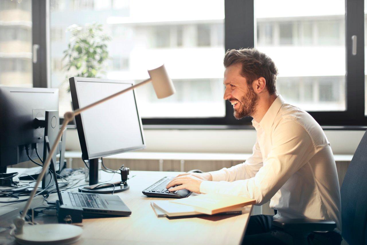 笑顔でパソコンをいじる男性