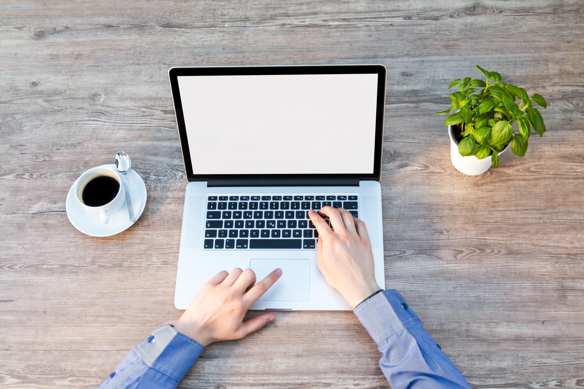 机の上にあるノートパソコンとコーヒーと植物