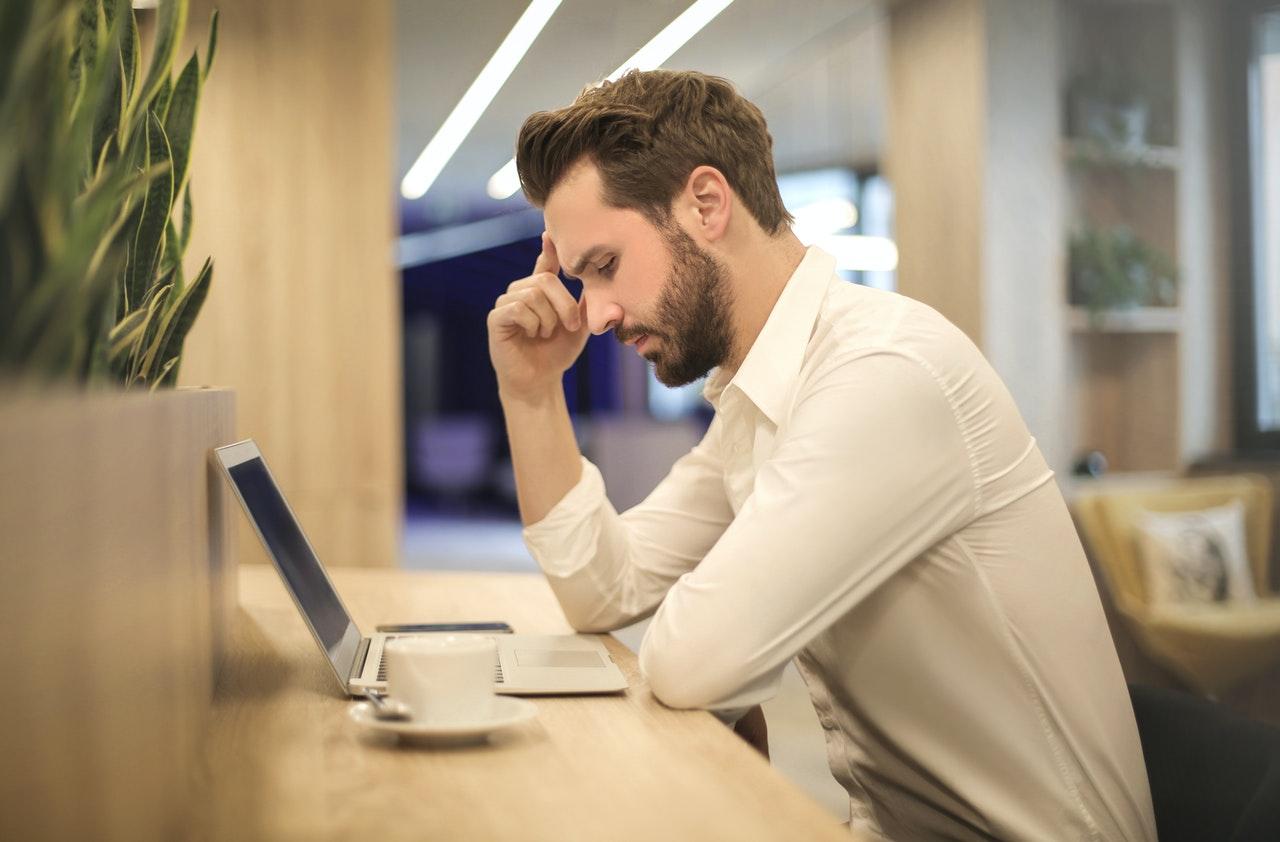 パソコンの前で頭に手をついて考える男性