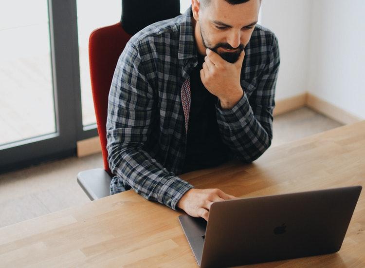 机でノートパソコンを触っている男性