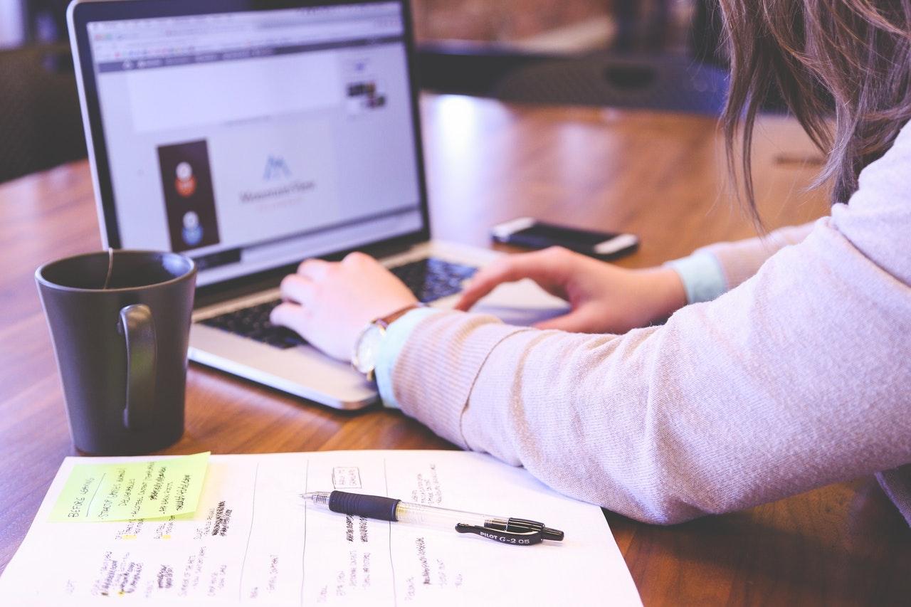机でパソコンをいじる女性