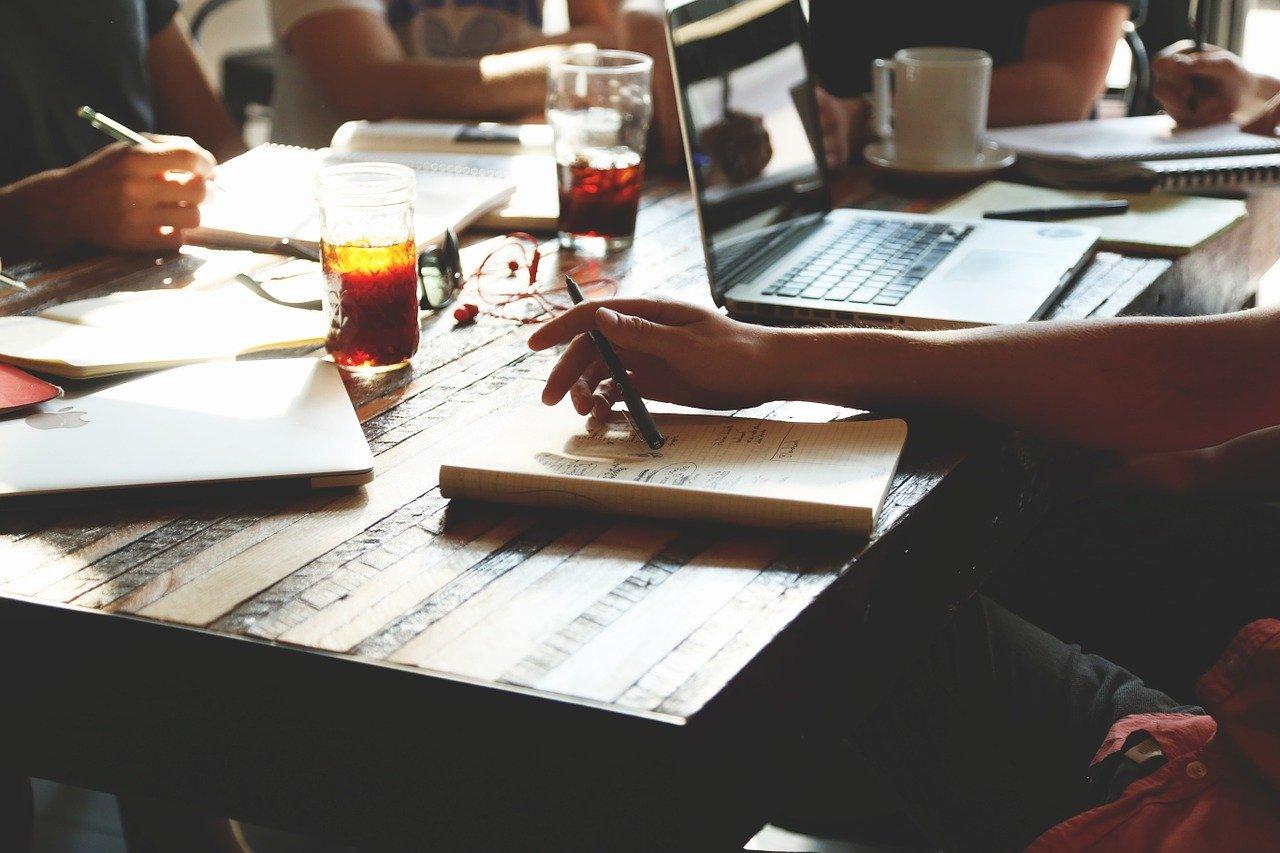 机の上でノートをとる人々