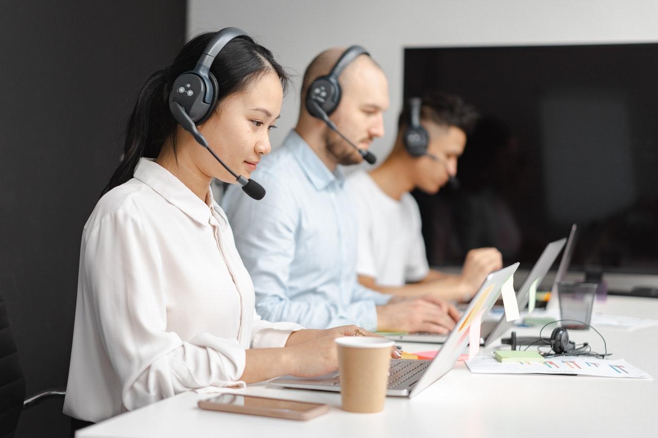 机に並んで仕事をする電話サポート