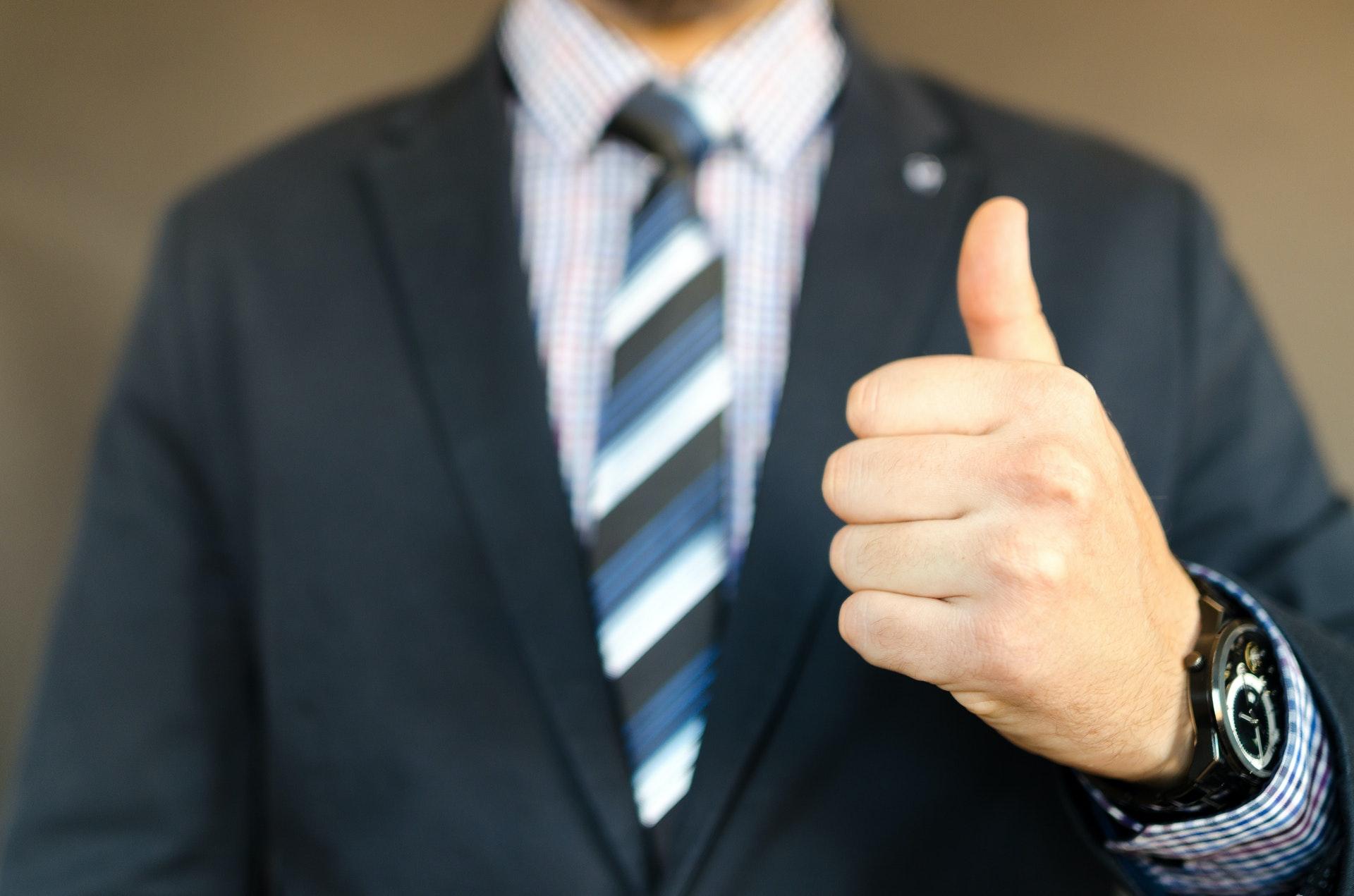 親指をたてるスーツの男性