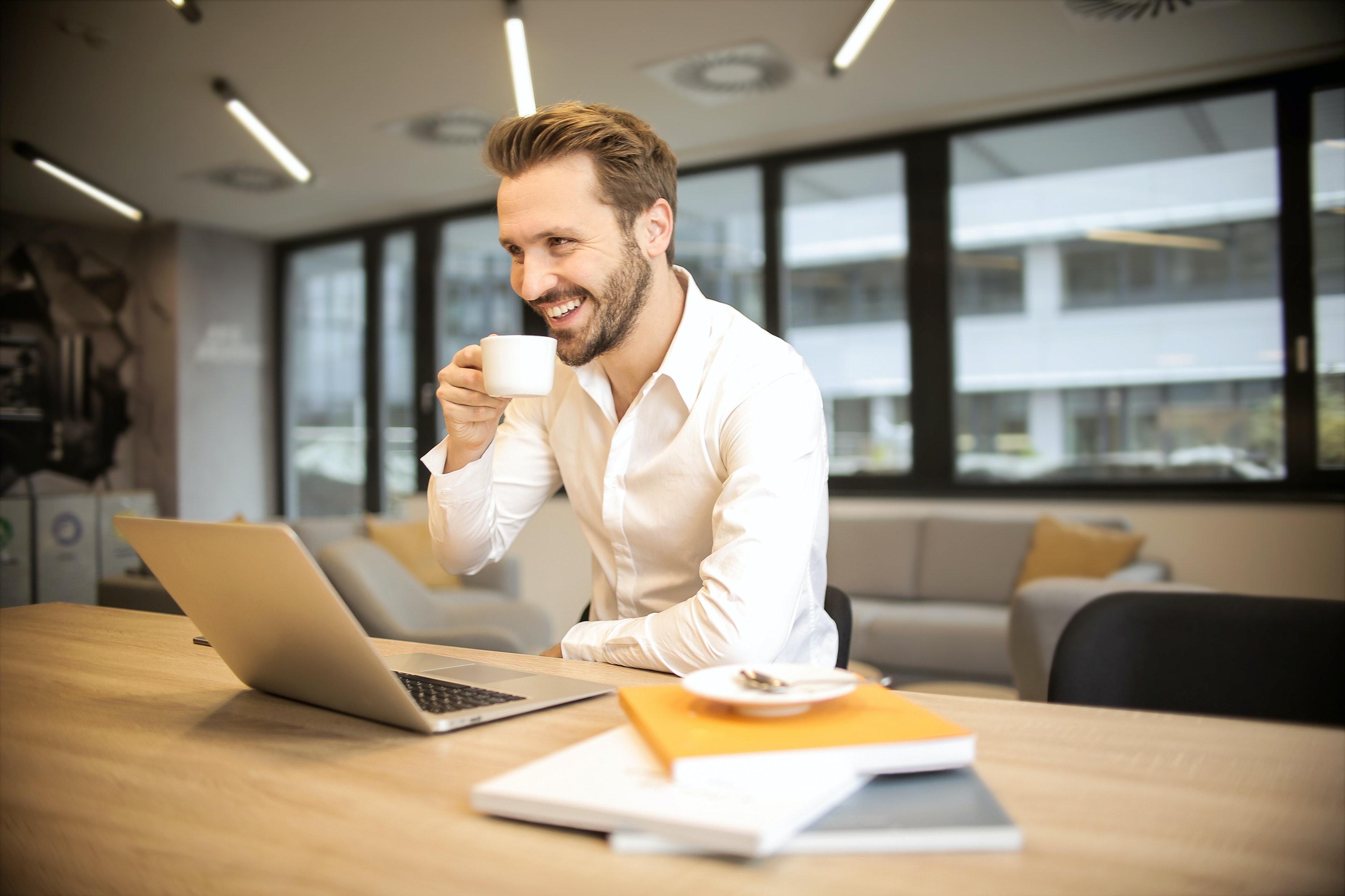 パソコンに向かって笑顔でコーヒーを飲む男性