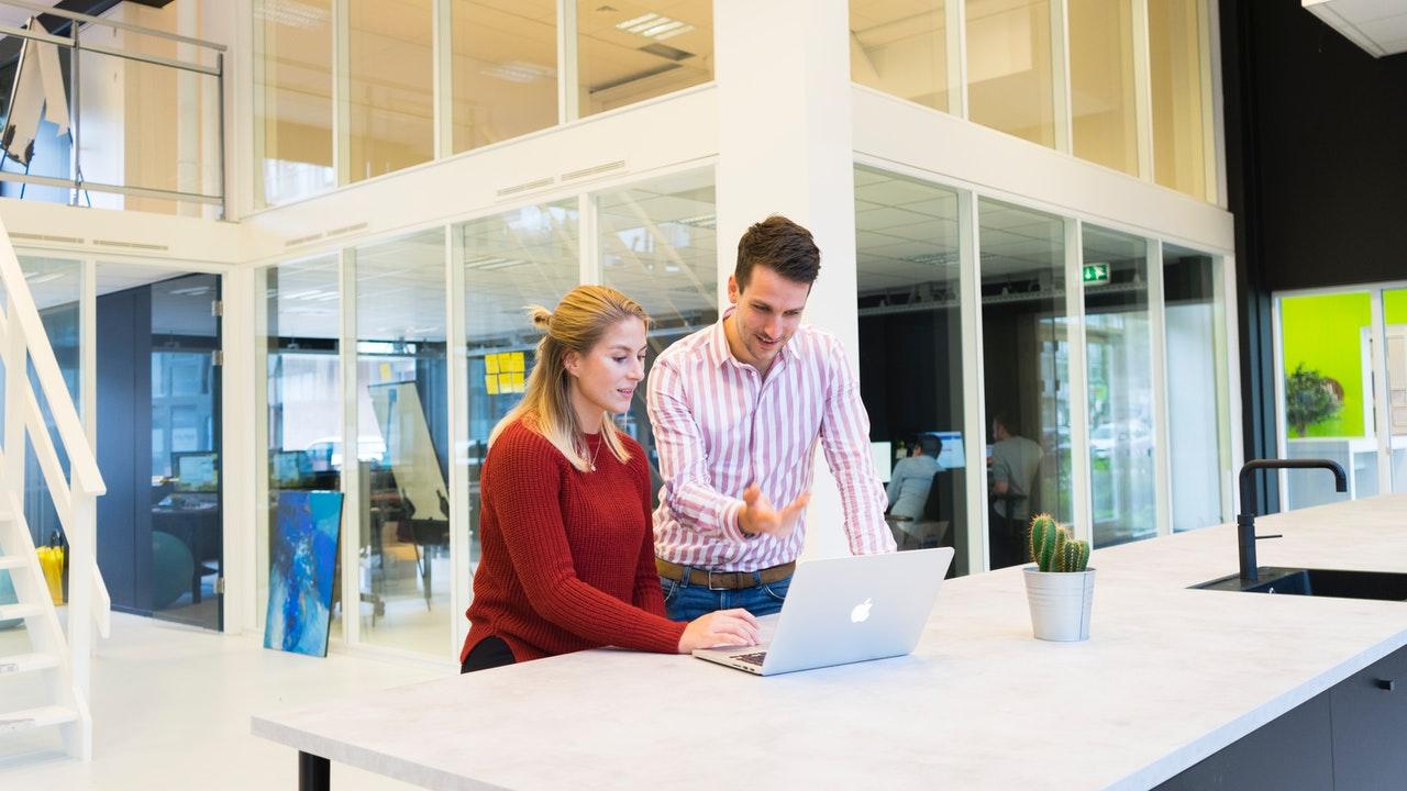 パソコンを見ながら会話をする男性と女性