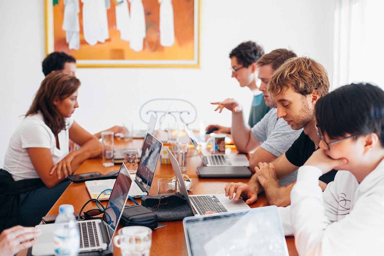 机に向かって話し合いをする人々