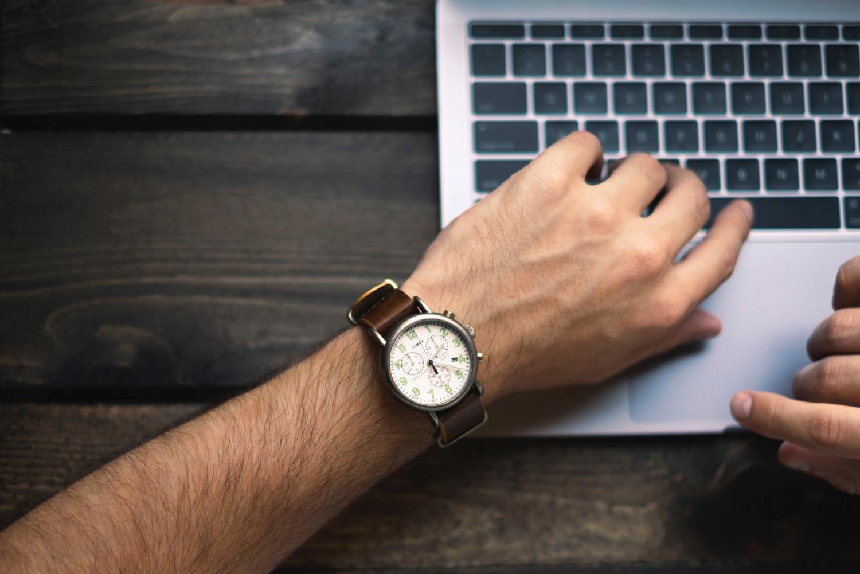 腕時計をしている男性の腕とノートパソコン