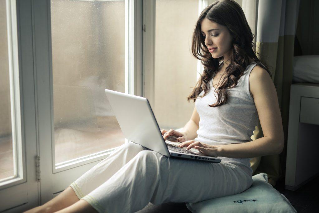 窓際でパソコンをいじる女性