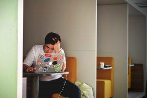パソコンをみながら頭を抱える男性