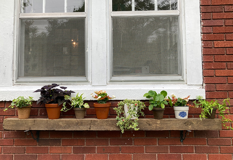 Houseplant Shelf: A worn piece of lumber and some brackets make an easy outdoor shelf for displaying houseplants.