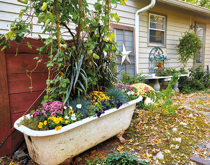 budget-friendly-garden-bathtub-planter: Pull the plug on the drain and leave holes for fixtures open for drainage, but cover them with fine mesh to prevent clogging.