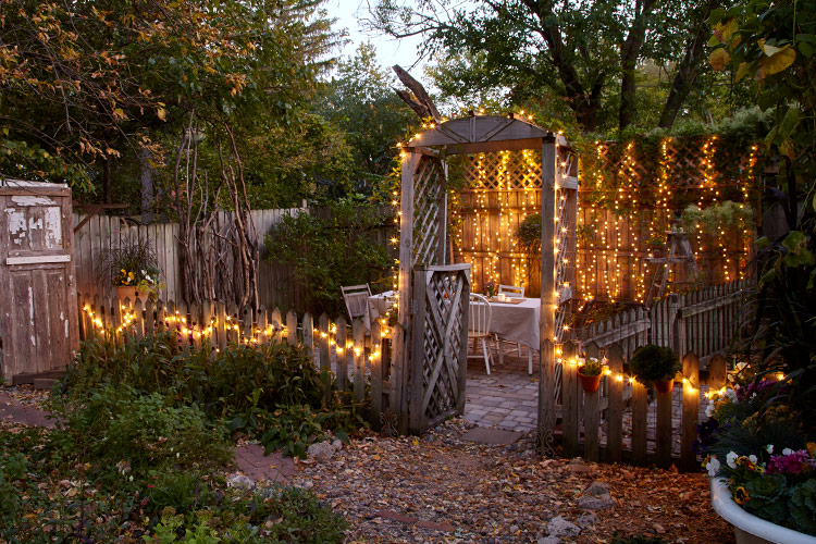 Add string lights to your garden for a warm glow:  Hang string lights on a fence with clips or tiny hooks. A timer makes turning on the lights hassle free — especially if your outlets are in difficult-to-reach places.