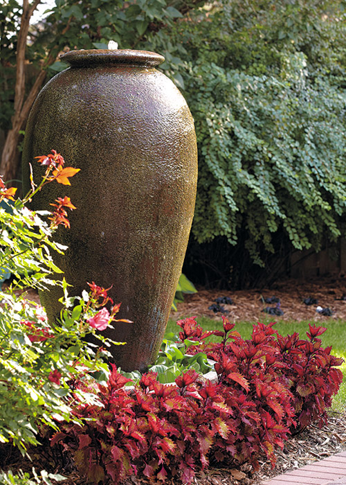 Henna coleus plants remain colorful all summer, making an attractive frame around this fountain.:Henna coleus plants remain colorful all summer, making an attractive frame around this fountain.