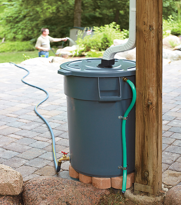 DIY Rain barrel made out of a heavy-duty trash can: Build a DIY rain barrel to save money on watering your garden.
